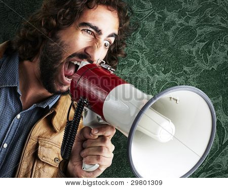 retrato de jovem gritando com megafone contra uma parede vintage