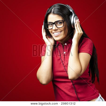 portrait of young woman listening to music against a red background