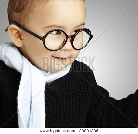 portrait of adorable kid gesturing doubt against a grey background