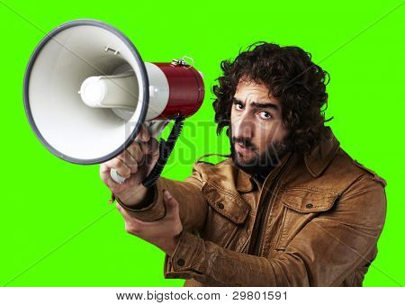 portrait of young man holding megaphone against a removable chroma key background