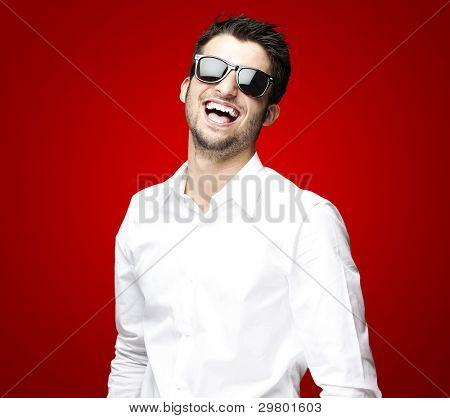 portrait of a handsome young man enjoying over red background