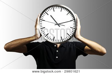 young man holding big clock covering his face over grey