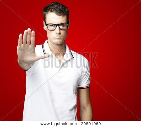 portrait of a handsome young man doing stop symbol over black background