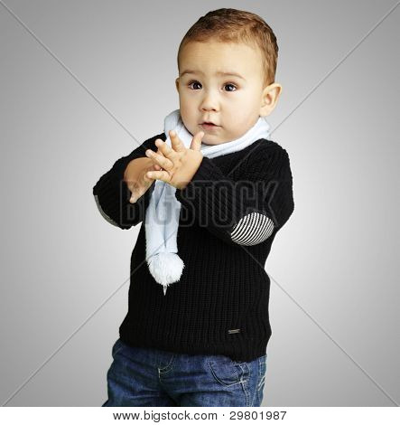 portrait of adorable kid clapping against a grey background