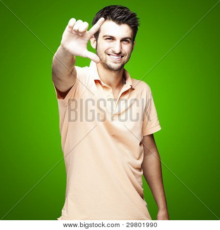 portrait of a handsome young man gesturing over green background