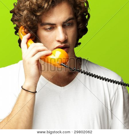 portrait of young man talking on a vintage telephone against a green background