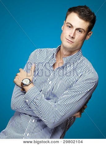 portrait of a handsome young man thinking over blue background