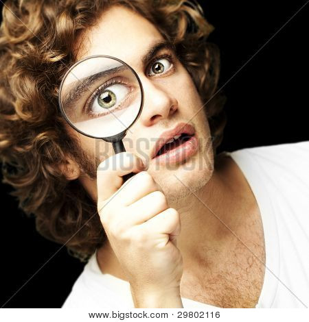 portrait of young man looking through a magnifying glass against a black background