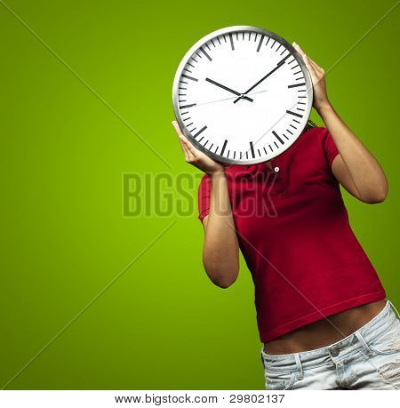woman holding clock in front of head against a green background