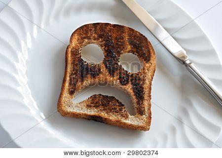traurig und unglücklich Smiley, gemacht aus geröstetem Brot mit Messer und Platte