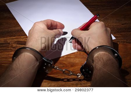 Man in handcuffs signing a document concept for coercion or being pressured into giving a signature or marriage