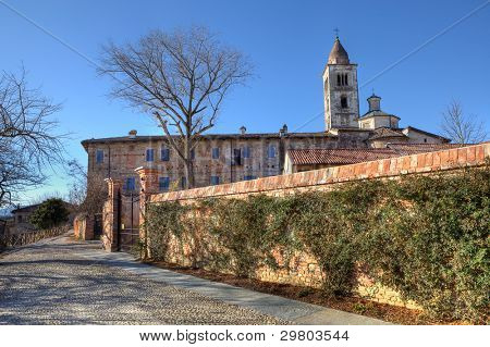 Ancient abandoned abbey and old church behind brick wall in town of La Morra, Northern Italy.