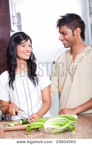 happy indian couple cooking in kitchen