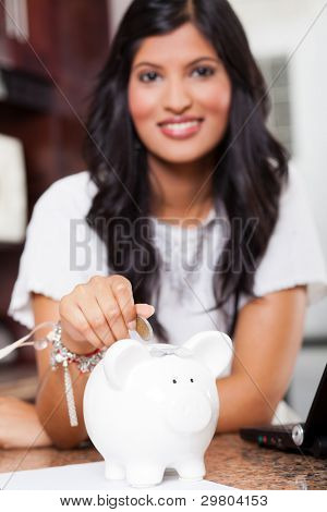 beautiful young indian woman putting a coin in piggy bank, focus on foreground