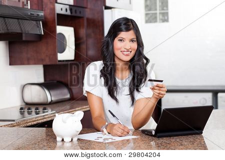 beautiful young indian woman paying credit cards bills