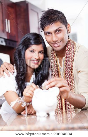 beautiful indian couple putting coins in piggybank