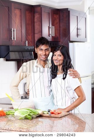 happy young indian couple hugging in kitchen