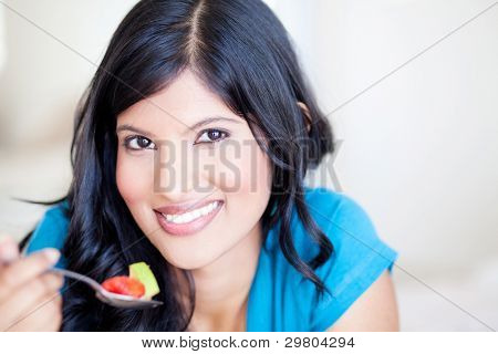 attractive healthy young woman eating fruit salad