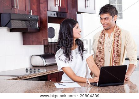 beautiful young indian couple using laptop at home
