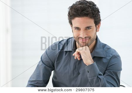 Satisfied proud business man looking at camera in the office with copy space