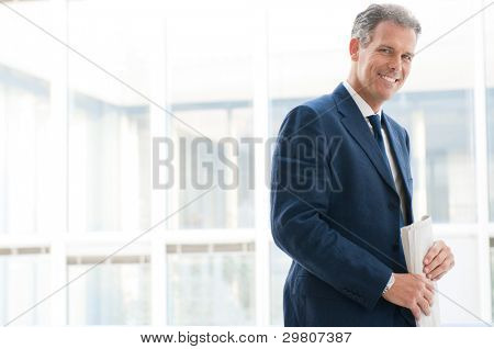 Smiling satisfied senior businessman looking at camera at office