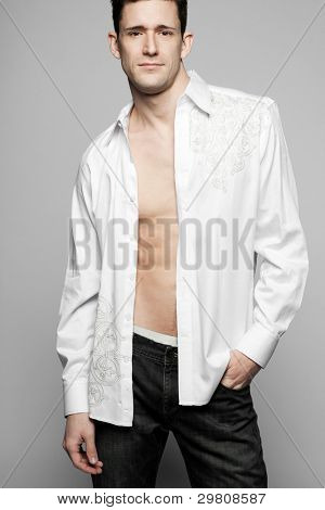 Young handsome fashion model posing in white shirt.