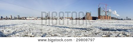 ultra wide panoramic view of the frozen Elbe river and Hamburg skyline