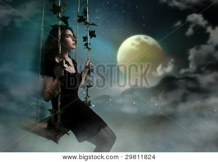 Beauty brunette swinging in night heaven