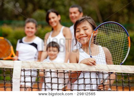 Girl tennis player with her family at the background