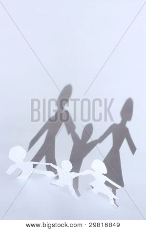 Paper people chain: man, woman and baby and shadows from them. F
