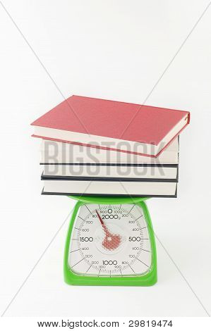Piled up books on a kitchen scale.