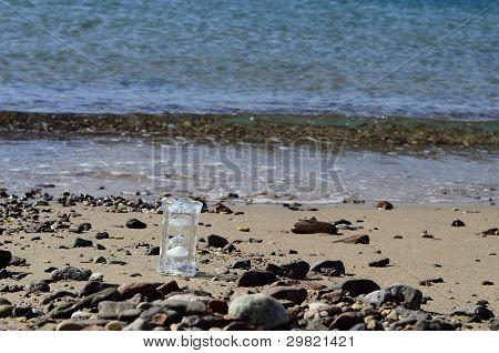 Crystal hourglass on marine beach