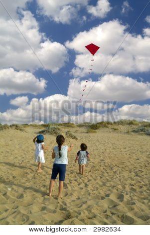 Tres niños y cometa roja