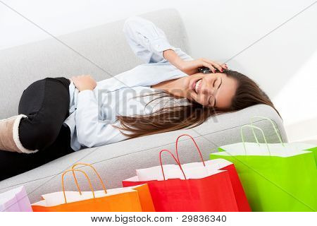 Happy Girl Laying On Couch With Mobile Phone