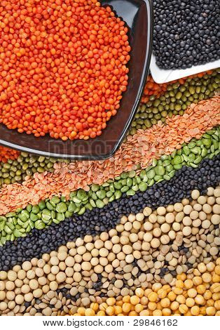 colorful striped rows of dry lentils, grain ,peas, groats , soybeans, legumes, rice, backdrop with  plate dish