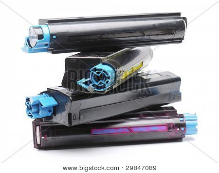 Pile of four used laser printer toner cartridges of Cyan, Magenta, Yellow and black color shot over white background