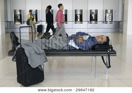 Businessman sleeping at airport
