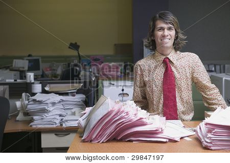 Portrait of a businessman standing behind a desk smiling