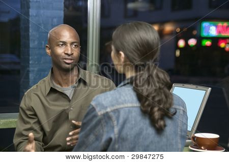 Couple with laptop talking at restaurant