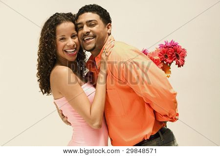 Portrait of man surprising girlfriend with flowers
