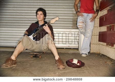 Young man playing guitar for money