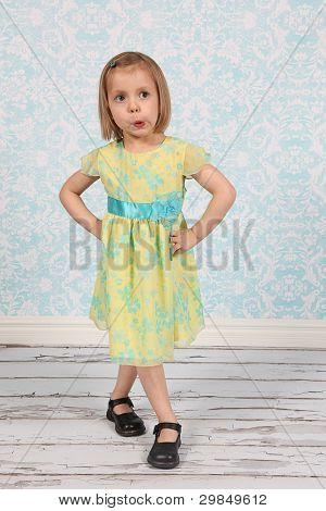 Adorable little girl making funny faces in studio