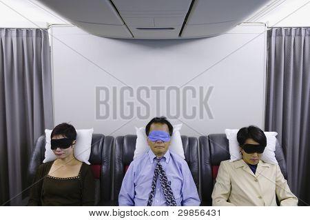 Three passengers sleeping on airplane