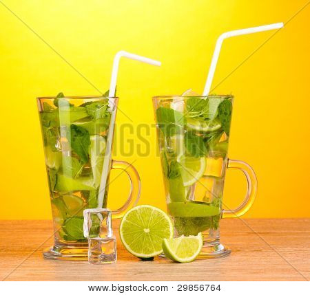 Glasses of cocktail with lime and mint on wooden table on yellow background