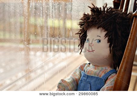 Handmade boy rag doll with cute sideways expression sitting alone next to a rainy window.  Closeup with shallow dof and copy space.