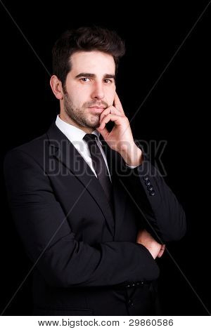 Handsome young business man portrait on black background