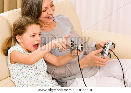 Grandmother play computer game with enthusiastic young girl have fun smiling