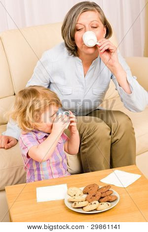 Little granddaughter with grandmother eat cookies drink tea cup together