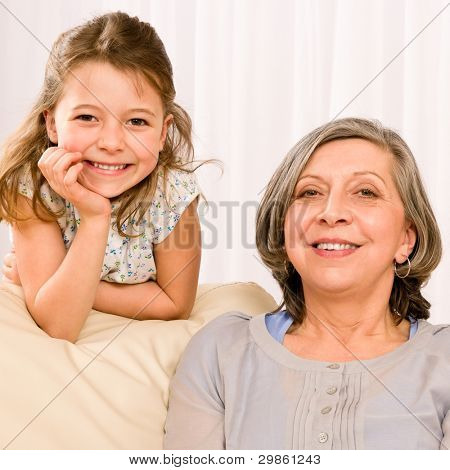 Grandmother with young girl smiling relax together on sofa