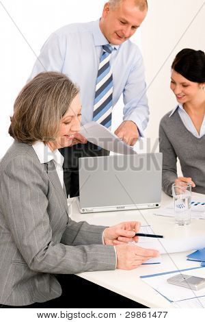 Business team meeting executive senior businesswoman with colleagues pointing report